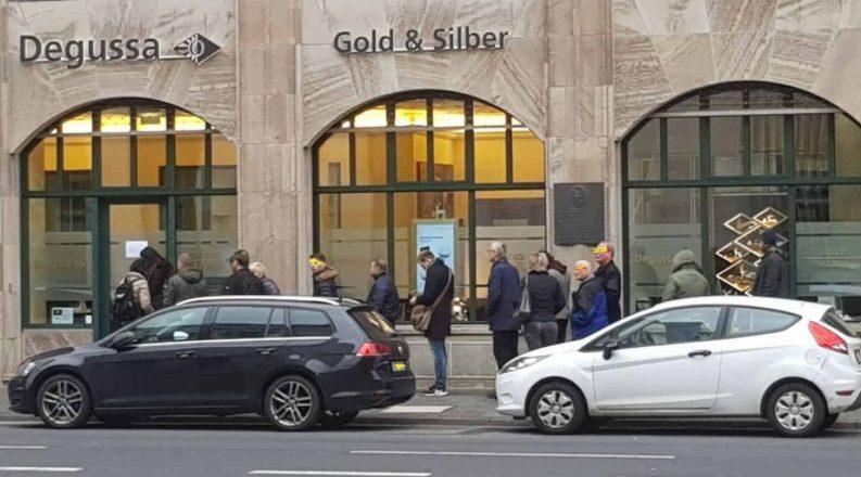 Schlange an Menschen vor einem Goldhändler Shop